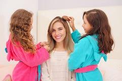 Schließen Sie oben von zwei kleinen Mädchen, die mit dem Haar ihrer Mutter spielen, während gelockte Mädchen ein rosa bathrope tr stockfotos