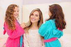 Schließen Sie oben von zwei kleinen Mädchen, die mit dem Haar ihrer Mutter spielen, während gelockte Mädchen ein rosa bathrope tr stockbilder