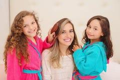 Schließen Sie oben von zwei kleinen Mädchen, die mit dem Haar ihrer Mutter spielen, während gelockte Mädchen ein rosa bathrope tr stockfotografie