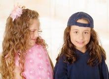 Schließen Sie oben von zwei Mädchen, wering man Jungenkleidung und anderes Mädchen trägt ein rosa Prinzessinkleid lizenzfreies stockbild