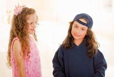 Schließen Sie oben von zwei Mädchen, wering man Jungenkleidung und anderes Mädchen trägt ein rosa Prinzessinkleid stockfotos