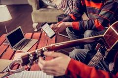 Schließen Sie oben von zwei Musikern, die nach etwas Melodie im Internet suchen stockfotografie