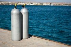 Schließen Sie oben von zwei Tauchflaschen, die unweit vom Wasser stehen stockfotografie