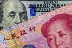 Schließen Sie oben 100 Yuan von der Banknote über der Banknote von hundert Dollar mit Fokus auf Porträts von Benjamin Franklin un Lizenzfreie Stockfotos