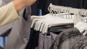 Schließen Sie oben, Zeitlupe Das Mädchen wählt Kleidung auf einem Aufhänger im Speicher Designer-Kleidung, moderne Kleidung stock footage