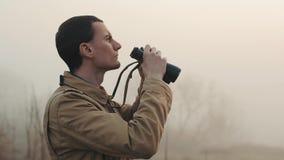 Schließen Sie vom jungen Rothaarigemann im kakifarbigen Mantel, der die Ferngläser hochhalten ist, die Sonnenaufgang und Sonnenun stock footage