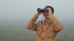 Schließen Sie vom jungen Rothaarigemann im kakifarbigen Mantel, der die Ferngläser hochhalten ist, die Sonnenaufgang und Sonnenun stock video