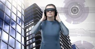 Schließen tragender Kopfhörer der virtuellen Realität der Frau und hohe Gebäude mit Sciencefiction Hintergrund an Stockfotos
