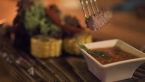 Schließen Sie herauf den Schnitt des Fleischsteaks während Abendessen im Abendrestaurant Frau, die gegrilltes Fleisch mit Tomaten stock video footage