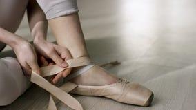 Schließen Sie oben für den Balletttänzer, der sich an setzt und Ballettschuhe binden Ballerina, die auf ihre pointe Schuhe sitzen lizenzfreie stockbilder