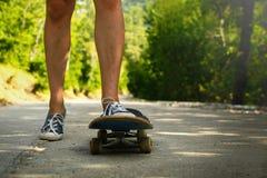 Schließen Sie oben von den Frauenbeinen in den Turnschuhen, die auf altem Skateboard stehen Ein Bein steht an Bord, das andere dr lizenzfreie stockfotografie
