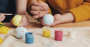 Schließen Sie oben von den Mutter- und Tochterhänden, die Ostereier mit Farben und Bürste färben Bunte Ostereier Vorbereitung von stock video footage
