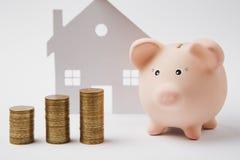 Schließen Sie oben von den rosa piggy Geldbankstapeln der goldenen Münzen auf weißem Wandhintergrund mit Haus Geldansammlung stockbild