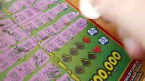 Schlie?en Sie herauf die Leute, die zu Hause Lottoschein verkratzen stock footage