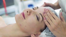 Schlie?en Sie herauf H?nde von Cosmetologist im Sch?nheitssalon, der Gesichtsmassage Frau mit geschlossenen Augen antut stock video footage