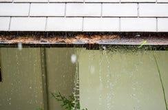 Schlie?en Sie oben auf dem Abschnitt der Regengosse verstopft mit Bl?ttern, R?ckstand auf Wohnheim w?hrend des Regens stockfoto