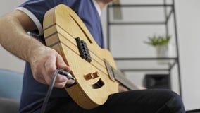 Schlie?en Sie oben vom Musiker, der in der E-Gitarre im Hauptmusikstudio verstopft stock video footage