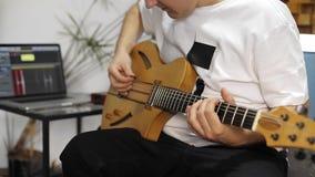 Schlie?en Sie oben vom Musiker, der in der E-Gitarre im Hauptmusikstudio verstopft stock footage