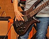 Schlie?en Sie oben von der Bass-Gitarre, die in einer Stadiumsleistung gespielt wird lizenzfreies stockfoto