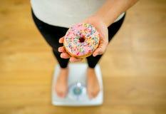 Schlie?en Sie oben von der Frau auf der Skala, die k?stlichen Donut in der Korpulenz und im ungesunden Nahrungsmittelkonzept h?lt lizenzfreie stockbilder