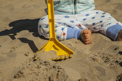 Schließen Sie herauf das Baby, das mit Sandspielwaren am Strand spielt Stockbild