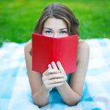 Schließen Sie herauf das Porträt der jungen Frau sein Gesicht hinter Buch versteckend Lizenzfreies Stockfoto