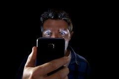 Schließen Sie herauf das Porträt des jungen Mannes intensiv schauend zum Handyschirm mit den blauen Augen, die breit sind, sich ö Lizenzfreies Stockbild