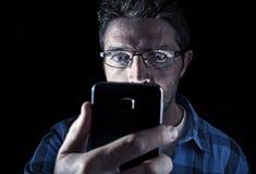 Schließen Sie herauf das Porträt des jungen Mannes intensiv schauend zum Handyschirm mit den blauen Augen, die breit sind, sich ö Stockfotografie