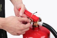 Schließen Sie herauf Feuerlöscher und Ziehenstift vom roten Behälter Stockfoto