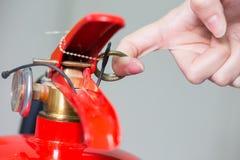 Schließen Sie herauf Feuerlöscher und Ziehenstift vom roten Behälter Stockfotos