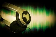 Schließen Sie herauf Kopfhörer, der Kopfhörer, der an Schallwelleschirmhintergrund gehangen wird Stockfotos