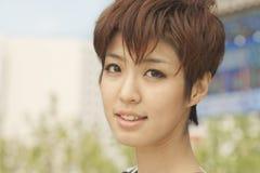 Schließen Sie herauf Porträt der jungen Frau mit dem Lächeln des kurzen Haares Lizenzfreie Stockbilder