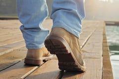 Schließen Sie oben auf den tragenden Holzfällerstiefeln des Mannes, die auf Dock gehen Starke schroffe männliche Art Jägerfischer Stockfoto