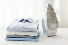 Schließen Sie oben vom Eisen und von der Kleidung auf Tabelle zu Hause Lizenzfreie Stockfotos