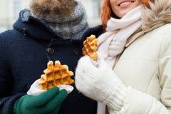 Schließen Sie oben vom glücklichen Paar, das draußen Waffeln isst Stockfoto