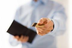 Schließen Sie oben vom Mann, der Geldbörse und Kreditkarte hält Stockbild