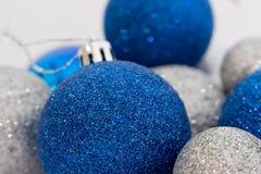 Schließen Sie oben vom Silber und von den blauen glänzenden Weihnachtsbällen Stockfotografie