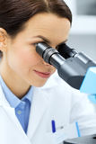 Schließen Sie oben vom Wissenschaftler, der zum Mikroskop im Labor schaut Stockfotografie