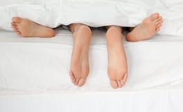 Schließen Sie oben von den Füßen des Paares in ihrem Bett Stockfotografie