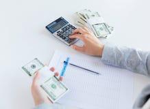 Schließen Sie oben von den Händen, die Geld mit Taschenrechner zählen Lizenzfreie Stockfotos
