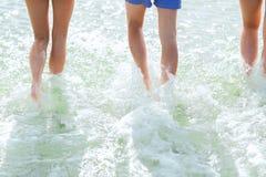 Schließen Sie oben von den menschlichen Beinen auf Sommerstrand Stockfotografie