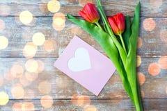 Schließen Sie oben von den Tulpen und von der Grußkarte mit Herzen Lizenzfreie Stockfotos