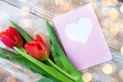 Schließen Sie oben von den Tulpen und von der Grußkarte mit Herzen Lizenzfreies Stockfoto