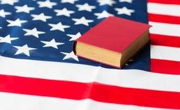 Schließen Sie oben von der amerikanischen Flagge und vom Buch Lizenzfreies Stockfoto