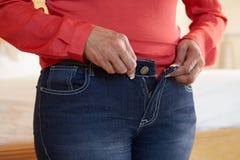 Schließen Sie oben von der überladenen Frau, die versucht, Hose zu befestigen Stockfoto