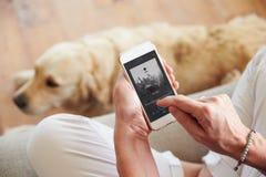 Schließen Sie oben von der Frau, die zu Hause Musik Smartphone hört Lizenzfreie Stockfotos