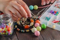 Schließen Sie oben von der Frauenhand, die Perlen verlegt Lizenzfreies Stockfoto