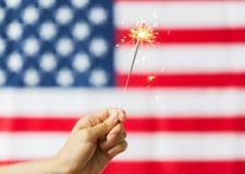 Schließen Sie oben von der Hand mit Wunderkerze über amerikanischer Flagge Stockbilder