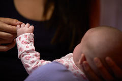 Schließen Sie oben von der Mutter, welche die Hand des neugeborenen Babys hält Stockbild