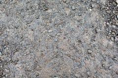 Schließen Sie oben von der nassen grauen Schotterstraße oder vom Boden Lizenzfreie Stockfotografie